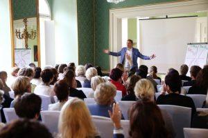 Ein Firmenevent im Schönbornsalon. Der Redner ist seinen Zuhörern zugewandt, im Hintergrund sehen wir seine Materialien und Präsentationsutensilien wie Leinwand und Whiteboard.