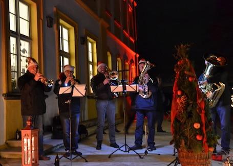 Blaskapelle spielt auf dem Weihnachtsmarkt mit fünf Mitgliedern.